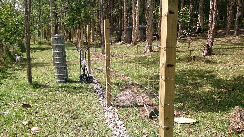 dog proof fence placing dog mesh onto posts.jpg