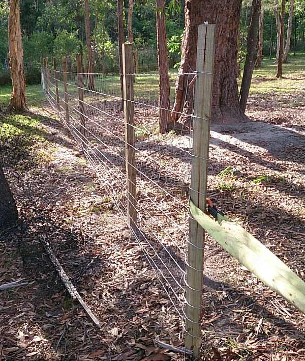 wire fence pulling to make taught fencing.jpg